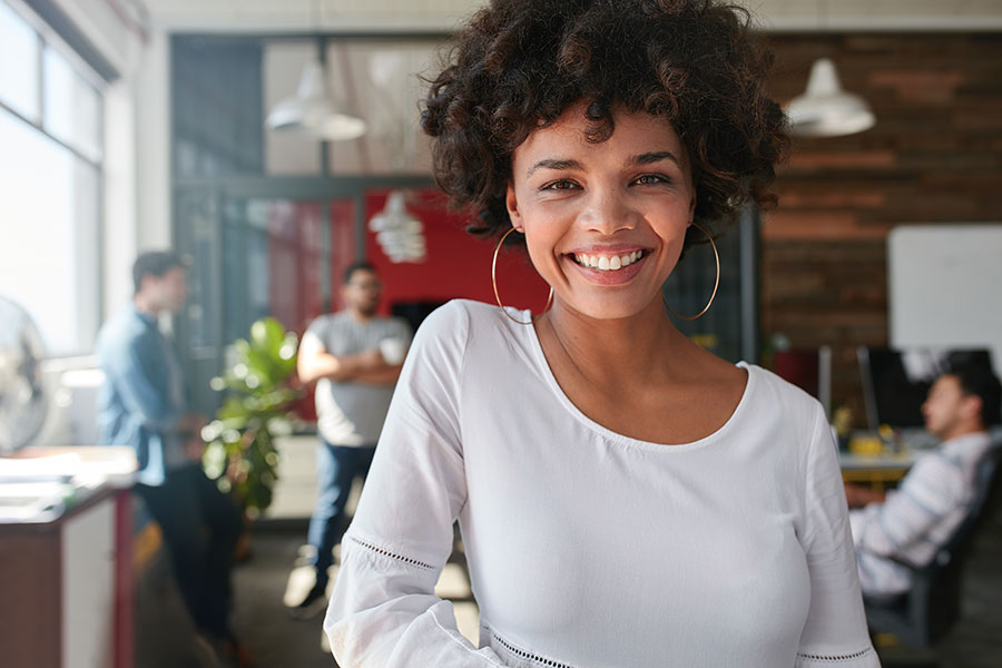 Business Insurance - African American Woman with Hoop Earrings Smiling with Business Team in Background